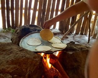 Maya woman cooking hand pressed corn tortillas, Aldea Ahau Chooc, Quintana Roo.